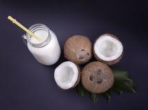 Verse, organische kokosnoten en een hoogtepunt van de metselaarkruik van natuurlijke kokosmelk met een geel stro op een donkerbla Stock Afbeeldingen