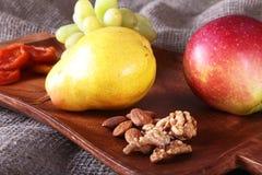 Verse organische vruchten op houten Dienend dienblad Geassorteerde appel, peer, druiven, droge vruchten en noten Stock Foto's