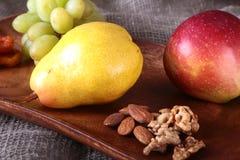 Verse organische vruchten op houten Dienend dienblad Geassorteerde appel, peer, druiven, droge vruchten en noten Royalty-vrije Stock Foto's