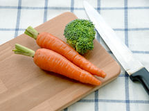 Verse organische wortelen en broccoli op oude houten raad stock foto's