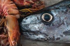 Verse overzeese vangst: grote grijze hoofdvissen met heldere gele ogen en zwarte leerling en een reusachtige oranje tijgergarnaal Stock Foto's