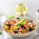 Verse panzanella van de tomatensalade met brood, olijf, peper en ui in de ceramische kom op keukenlijst met oliefles royalty-vrije stock afbeeldingen
