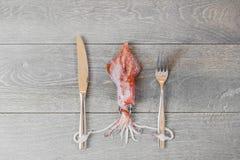 Verse pijlinktvis op houten lijst met vork en mes Royalty-vrije Stock Fotografie