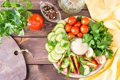 Verse plakken van komkommers, tomaten, sesamzaden in een kom Royalty-vrije Stock Afbeeldingen