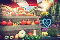 Verse pompoenen en bloemen bij lokale landbouwersmarkt Stock Foto's