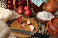 Verse producten voor een gezonde voeding op het kok` s bureau: pompoen, pompoen, sappige appelen, tarwemeel, een kruik melk, olij Stock Fotografie