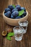 Verse pruimen en pruimbrandewijn op houten lijst stock fotografie