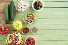 Verse rauwe groenten en salades in kommen op houten lijst stock afbeeldingen
