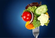 Verse rauwe groenten op vork op blauwe achtergrond stock foto's