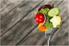 Verse rauwe groenten op vork op houten achtergrond stock fotografie