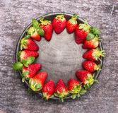 Verse rijpe aardbeien in plaat op grijze houten achtergrond, voedselkader, hoogste mening Stock Afbeelding