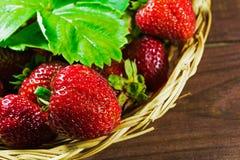 Verse rijpe aardbeien in rieten mand op oude houten backgroun Stock Foto