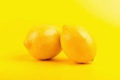 Verse rijpe die citroenen op gele achtergrond worden geïsoleerd Stock Afbeeldingen