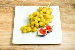 Verse rijpe fig. en druiven in een kom stock afbeelding
