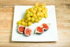 Verse rijpe fig. en druiven in een kom stock fotografie