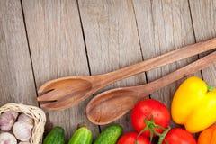 Verse rijpe groenten en werktuigen op houten lijst stock afbeelding