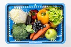 Verse rijpe groenten in het winkelen mand op wit Stock Afbeeldingen