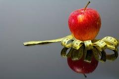 Verse rode appel met dalingen van water op een metende band met spiegelbezinning Stock Afbeelding