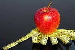 Verse rode appel met dalingen van water op een metende band met spiegelbezinning Royalty-vrije Stock Foto