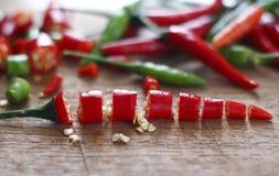 Verse rode en groene Spaanse pepers en gehakte verse rode en groene Spaanse pepers op houten hakkend blok Royalty-vrije Stock Afbeeldingen