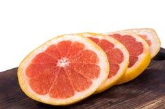 Verse rode grapefruitringen geplaatst die op houten raad op witte achtergrond worden geïsoleerd Stock Foto's