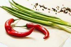 Verse rode Spaanse peperpeper en groene uien op een witte achtergrond stock afbeeldingen