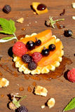 Verse rode, zwarte framboos en bes, perzik, honingsdaling op wafel op houten dichte omhooggaand als achtergrond Stock Afbeelding