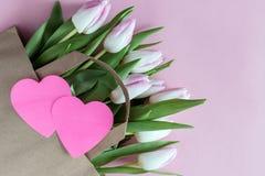 Verse roze tulpenbloemen in document zak met document hart royalty-vrije stock afbeeldingen