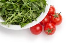 Verse rucolabladeren in een kom en tomaten royalty-vrije stock foto's