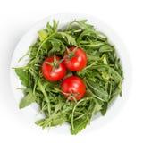Verse rucolabladeren in een kom met tomaten royalty-vrije stock foto