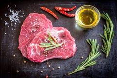 Verse rundvleeslapjes vlees met ingrediënten op de donkere achtergrond Royalty-vrije Stock Foto's