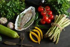 Verse ruwe doradavissen in een witte schotel met een reeks groenten op een zwarte lijst stock fotografie