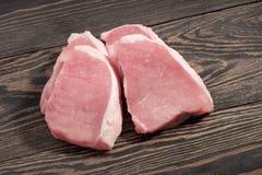 Verse ruwe varkensvleeslapjes vlees op een donkere houten achtergrond Royalty-vrije Stock Foto