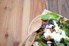 Verse salade in houten plaat op houten lijst Stock Foto