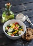 Verse salade met tomaten, komkommers, peper, olijven en kaas in een ceramische kom Stock Afbeelding