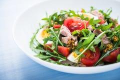 Verse salade met tonijn, tomaten, eieren, arugula en mosterd op blauwe houten dichte omhooggaand als achtergrond Royalty-vrije Stock Fotografie