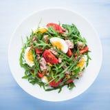Verse salade met tonijn, tomaten, eieren, arugula en mosterd op blauwe houten hoogste mening als achtergrond Stock Fotografie