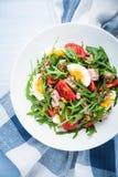 Verse salade met tonijn, tomaten, eieren, arugula en mosterd op blauwe houten hoogste mening als achtergrond Royalty-vrije Stock Fotografie