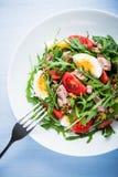 Verse salade met tonijn, tomaten, eieren, arugula en mosterd op blauwe houten hoogste mening als achtergrond Royalty-vrije Stock Afbeelding