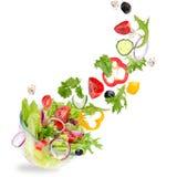 Verse salade met vliegende groenteningrediënten stock afbeelding