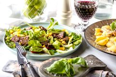 Verse saladeplaat met gemengde greens dicht omhoog arugula, mesclun, mache op donkere houten achtergrond MANZO stock afbeelding