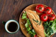 Verse sandwich met sla, tomaten, kaas op houten plaat, kop van koffie op houten achtergrond, selectieve nadruk Stock Foto