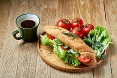 Verse sandwich met sla, tomaten, kaas op houten plaat, kop van koffie op rustieke achtergrond, selectieve nadruk Stock Foto's