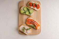 Verse sandwiches met zalm, komkommer, tomaten, avocado's en greens royalty-vrije stock foto's