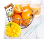 Verse sappige de zomervruchten, sinaasappelen, mango, kiwi in een uitstekende mand en verfrissingdranken op een houten lijst aang Royalty-vrije Stock Foto