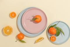 Verse sappige mandarijnen, granaatappels en gesneden vruchten op een gele achtergrond De zomerstemming, gezond voedsel Hoogste me royalty-vrije stock foto's