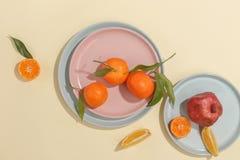 Verse sappige mandarijnen, granaatappels en gesneden vruchten op een gele achtergrond De zomerstemming, gezond voedsel Hoogste me stock afbeeldingen