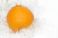 Verse, sappige sinaasappel die in koel water springen. Stock Afbeeldingen