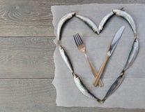 Verse sardine in hartvorm en bestek Stock Afbeelding