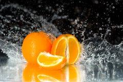 Verse sinaasappel op zwarte achtergrond met stromend water op het mir Stock Fotografie